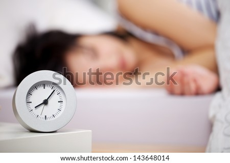 Close up image of alarm clock over the blurred sleeping woman - stock photo