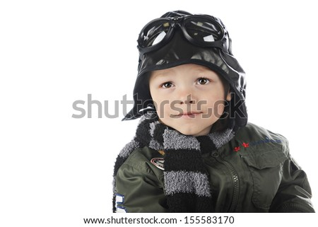 "Close-up image of an adorable toddler playing ""old-time pilot"" in his olive green jacket, pilot hat,scarf and goggles with space on the left for your text."