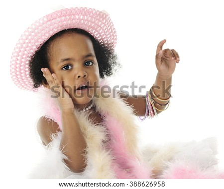Close-up image of an adorable 2 year old diva in beads, boas and bangles.  She's looking at the viewer with one hand on her cheek.  On a white background. - stock photo