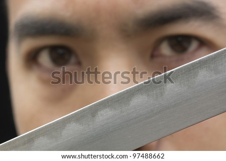 Close up image of an Asian man looking passed a samurai sword blade. - stock photo