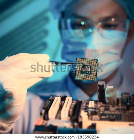 Close-up image of an it-engineer with chip holding in tweezers on the foreground  - stock photo