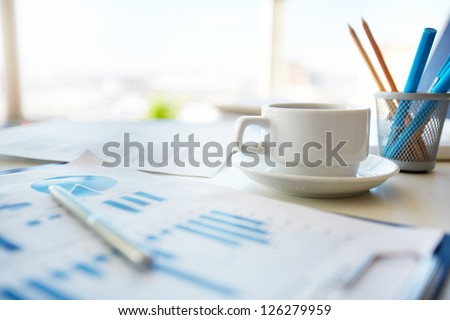 Close-up image of an office desk at morning with a cup of tea and financial documents