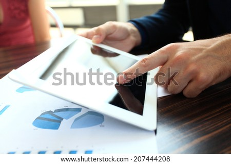 Close-up image of an office worker using a touchpad to analyze statistical data  - stock photo