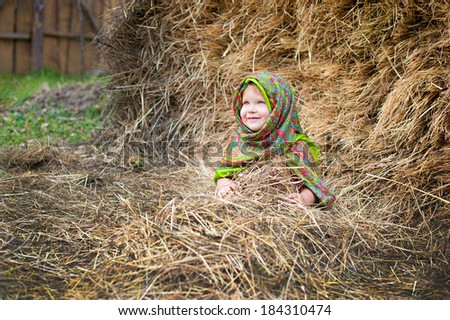Close up image of beautiful little girl in russian village traditional kerchief with round cracknel with russian ornamen over autumn weather/Lovely russian young gir - stock photo