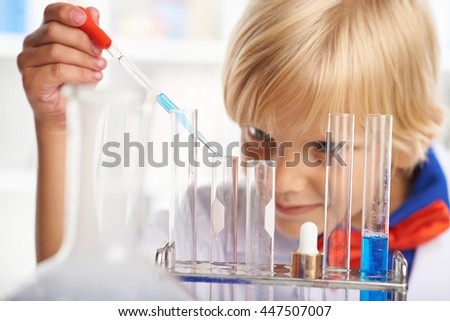 Close-up image of boy adding liquid in test-tube