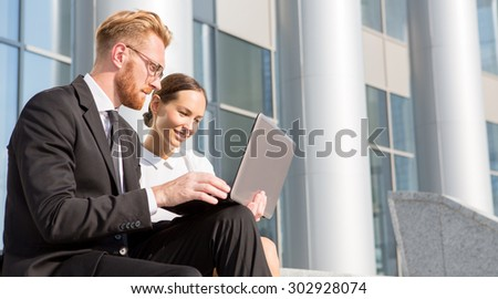 Close-up image of business colleagues networking together in front of office buiding. Man and woman discussing problems, issuies, ideas, strategies. - stock photo