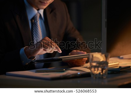 Close-up image of business person using tablet computer in dark office