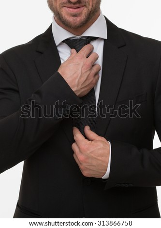 Close-up image of businessman adjusting his expensive tie isolated on white. Handsome man in black business suit in studio. - stock photo