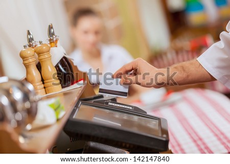 Close-up image of cashier male hands holding card - stock photo