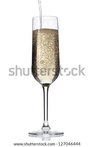 Close-up image of champagne falling in champagne flute over plain white background.