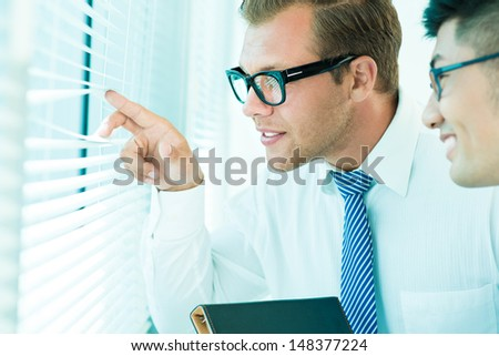 Close-up image of cheerful business people peeping through the blinds - stock photo