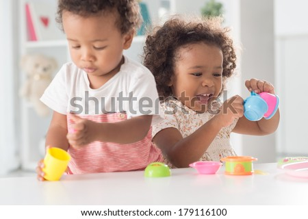 Close-up image of cheerful little girl playing with toys with her brother on the foreground  - stock photo