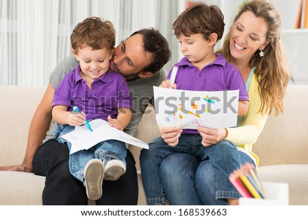 Close up image of cheerful parents drawing with their children at home