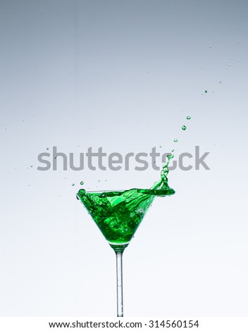 Close up image of cocktails splashing in a martini glass shot on a white background in studio.