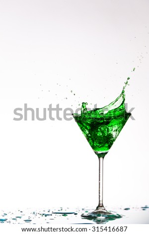 Close up image of cocktails splashing in a martini glass shot on a white background in studio