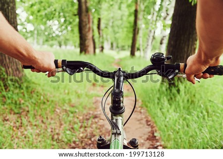Close-up image of cyclist man hands on handlebar riding mountain bike on trail in summer park, face is not visible - stock photo