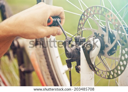 Close-up image of cyclist's hand repairs wheel of bicycle - stock photo