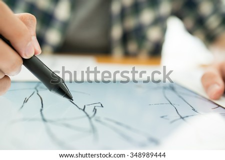 Close-up image of designer using stylus to draw sketch on digital tablet - stock photo