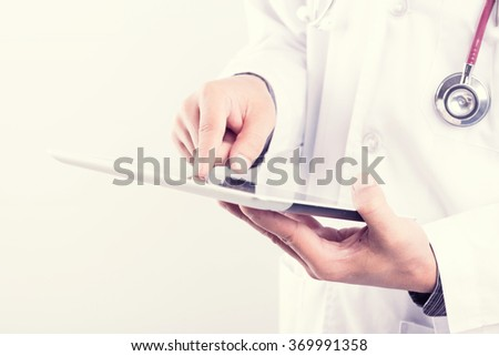 Close up image of doctor using digital tablet pc : vintage filtered process - stock photo