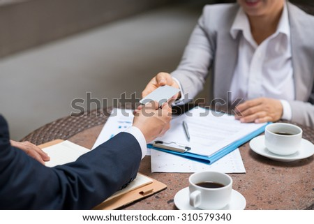 Close-up image of entrepreneur giving business card to his colleague - stock photo