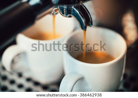 Close up image of espresso pouring into white cups - stock photo