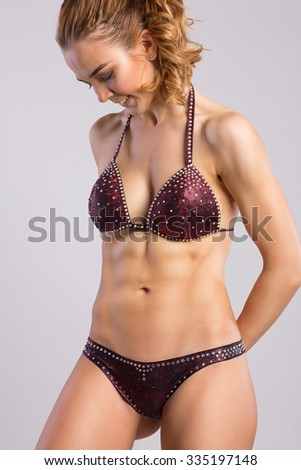 Close up image of European female in sports clothing relaxing after workout on grey background. Muscular female body - stock photo