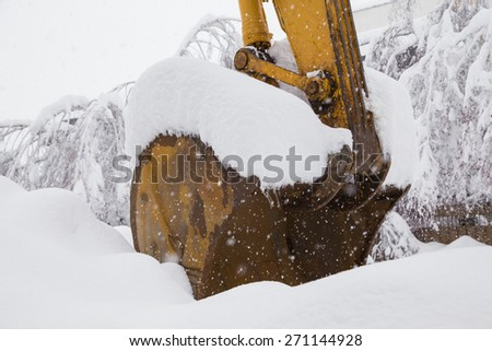 Close-up image of excavator shovel covered with snow. - stock photo