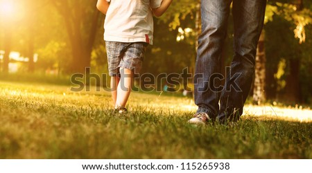 Close up image of father and son legs walk across the lawn in the park - stock photo