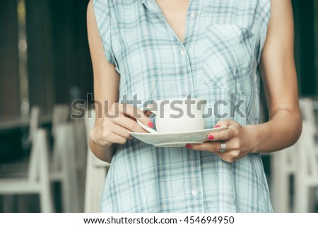 Close up image of female hands holding white ceramic cup