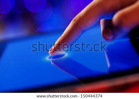 Close-up image of finger touching blue screen