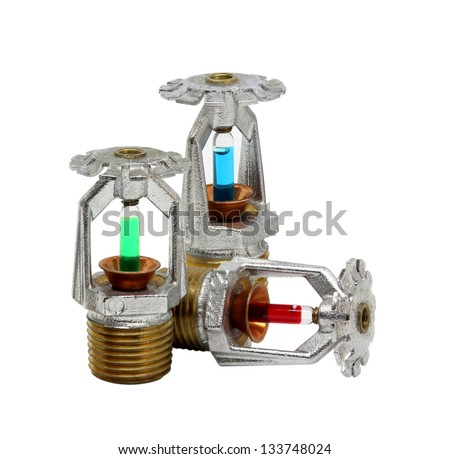 Close up image of fire sprinkler with fire in background. Fire sprinklers are part of an integrated water piping system designed for life and fire safety. - stock photo