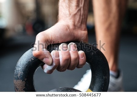 Close up image of fitness hand and kettlebell. preparing to raise