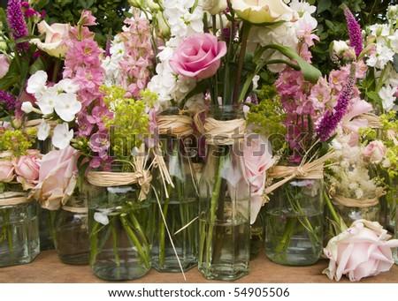 close up image of flower arrangements in jam jars - stock photo