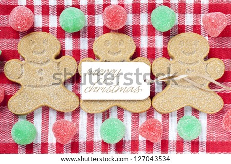 Close-up image of gingerbread candies with merry Christmas tag over red napkin.