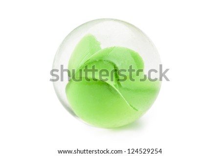 Close up image of glass marble with green swirl inside against white background