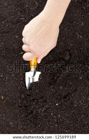 Close-up image of hand holding a shovel cultivating the soil