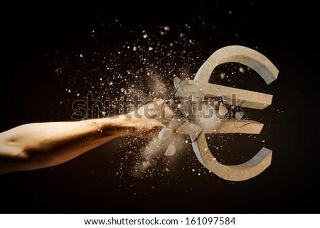 Close up image of human hand breaking euro stone symbol - stock photo