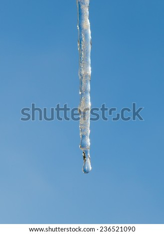 Close-Up Image of Icicle with Drop of Water on the Clear Blue Sky Background - stock photo