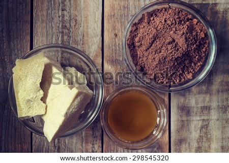 Close up image of ingredients of chocolate: cocoa butter, cocoa powder and honey on grunge wooden background - stock photo