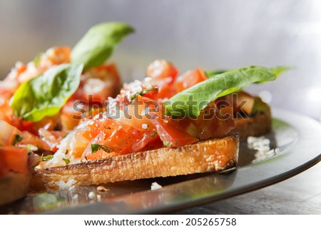Close-up image of italian bruschetta with tomatoe and basil on a serving plate - stock photo