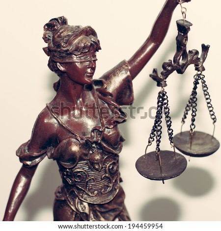 close up image of lady justice or themis holding scale blindfold on white background - stock photo
