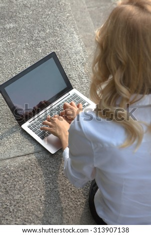 Close-up image of laptop computer. Blond woman using laptop computer outdoors for working. Lady sitting on brick wall in the park. - stock photo
