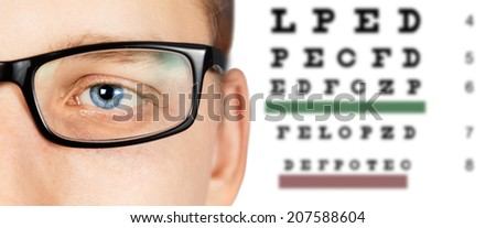 Close-up image of male eye in glasses on background of eyesight test