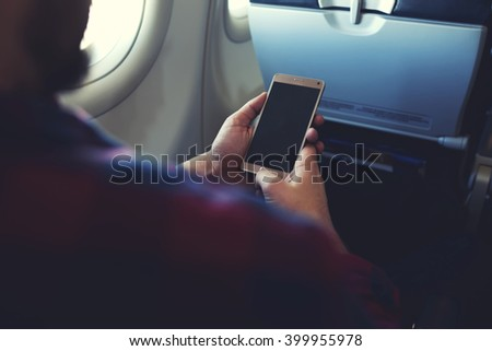 Close up image of man`s hands is holding cell telephone with blank copy space screen for your promotional content. Hipster guy is reading text message on mobile phone during flying in an airplane - stock photo