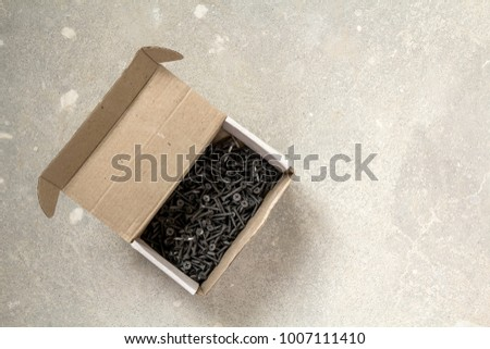 Close-up image of many small black screws on concrete background