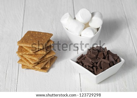Close up image of marshmallow, crackers and chocolate on wooden table - stock photo