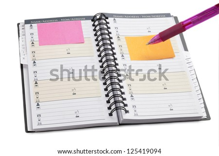 Close up image of note book organizer with pink ball pen and adhesive note on white background
