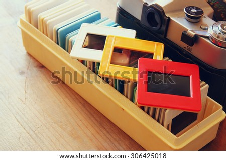 close up image of old slides frames and old camera over wooden table - stock photo