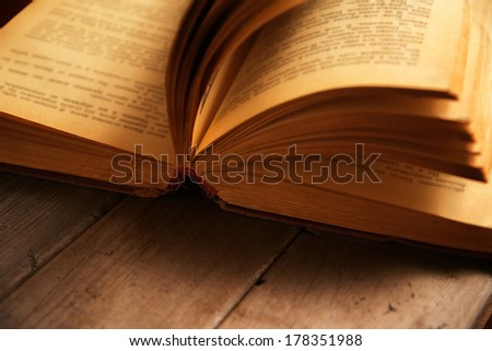 Close-up image of open book on a wooden table