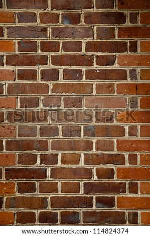 Close up image of Orange and brown brick wall.  concrete seperation between each brick is visible - stock photo